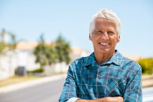 Retired old man standing outdoor with folded arms smiling and looking at camera. Successful mature man relaxing outdoor with copy space. Portrait of happy senior grandfather with crossed arms and big grin on face.