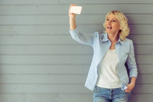 Beautiful mature woman in casual clothes is making a selfie using phone and smiling, standing against gray background