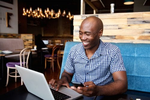 Portrait of smiling man with a mobile phone sitting at cafe using laptop